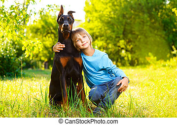 boy hugs his beloved dog or doberman in summer park.