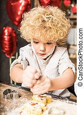 Boy icing cookies