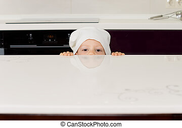 Boy in a chefs hat peering over the counter