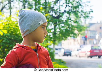 boy in a hat peering into the road