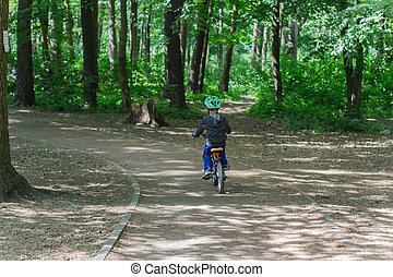 boy in a helmet on a bicycle in the park