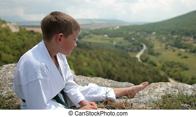 boy in a kimono sits resting on the edge of the cliff