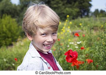 Boy in a poppy field, springtime