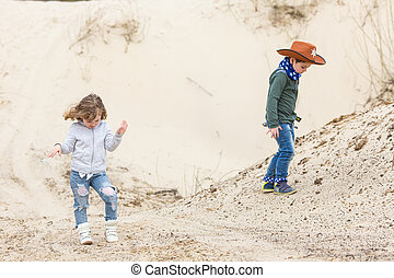 boy in a sheriff hat with a gun walks with a girl