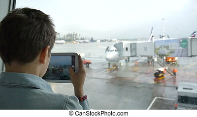 Boy in airport pictures of airplanes on the tablet - Young...