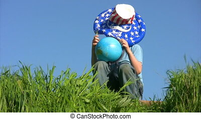 boy in american flag hat sits and holds globe