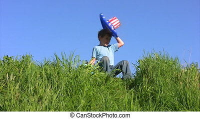 boy in american flag hat sits on grass and holds globe - boy...