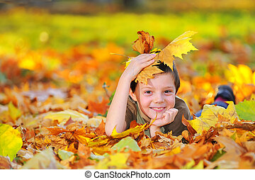 boy in autumn forest playing with leaves