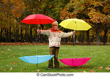 Boy in autumn park. Has control over four multi-coloured umbrellas.