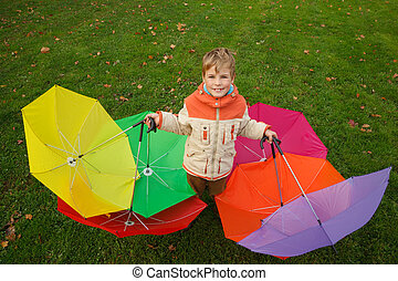 Boy in autumn park, in environment of multi-coloured umbrellas. Top view. Horizontal format.