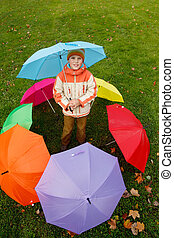 Boy in autumn park, in environment of multi-coloured umbrellas. Top view.