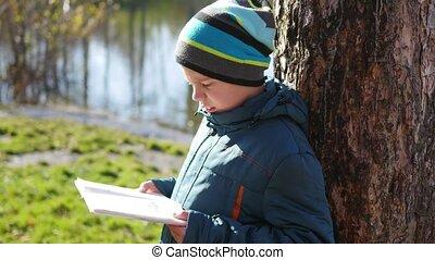Boy in autumn Park near the lake reading a book. A beautiful autumn landscape. School education