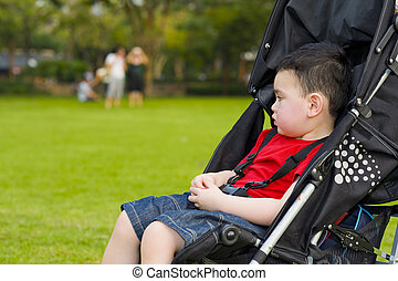 boy in baby buggy - cute boy out in the green day-dreaming...