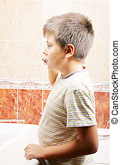 Boy in bathroom brushing teeth