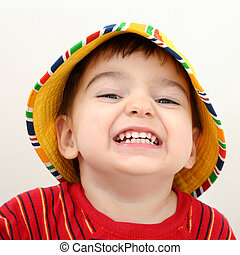 Sweet and very happy 2 year old boy in a yellow and stripe beach hat. Shot with the Canon 20D.