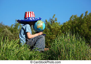 boy in big american flag hat sits on  grass and holds globe