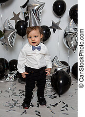 boy in black clothes on his birthday party with balloon