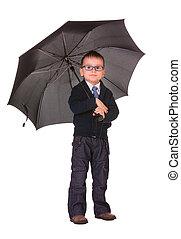 Boy in black clothes standing under umbrella