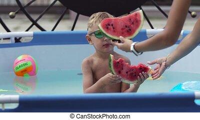 Boy in black glasses eats watermelon in the pool