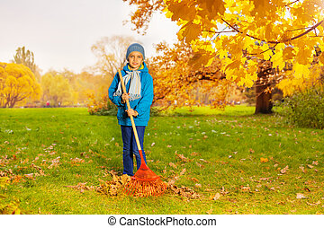 Boy in blue jacket with rake cleaning grass