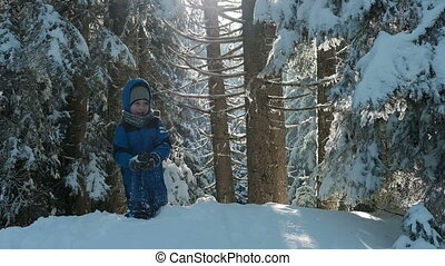 Boy in blue overalls on the hill playing snowballs in winter wood.