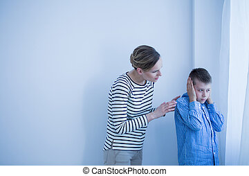 Boy in blue shirt doesn't want to hear while his mother in...