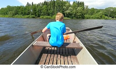 Boy in blue with life jackets at legs floats on vessel boat ...