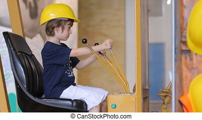 Boy in builder helmet sitting in excavator