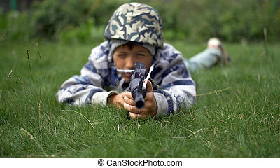 boy in camoflauge playing war shoots a toy gun