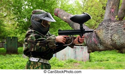 Boy in camouflage stand in shooting position and put paintball gun on tree branch