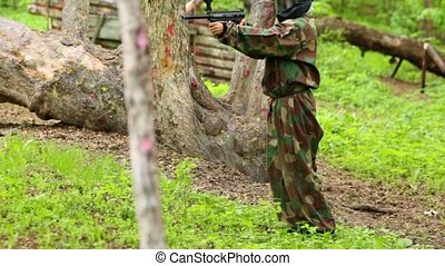 Boy in camouflage stand with paintball gun and then run away