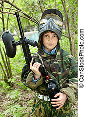 Boy in camouflage stands against brushes on the paintball area raising his paintball gun up and looks straight ahead.