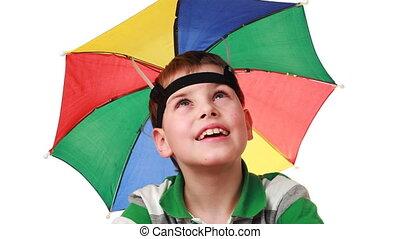 boy in cap as umbrella rainbow colors happily smiles, white...