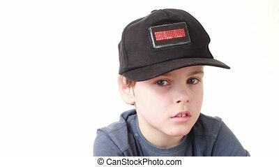 boy in cap with word Hello on red LED display grieves