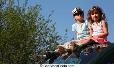 Boy in captain's cap and his sister sit on roof of car