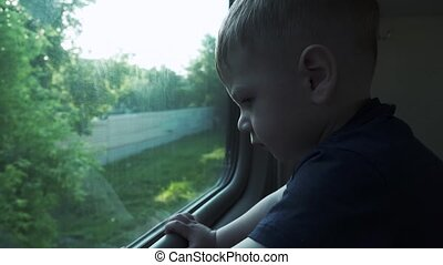 A boy in a reserved seat car looks out the window