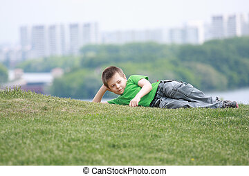 Boy in casual laying down on grass