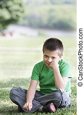 Boy in casual on grass leaning on fist