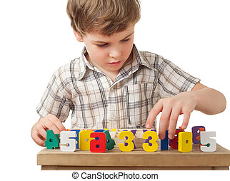 boy in checkered shirt displays wooden figures in form of numerals on table isolated on white background