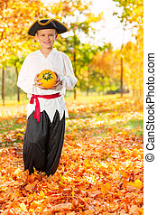 Boy in costume of pirate hold small pumpkin