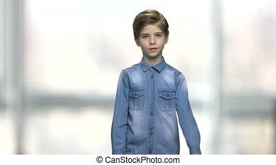 Boy in denim jacket giving thumb up. Cute little boy...