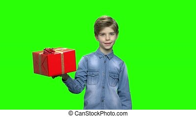 Boy in denim jacket holding red gift box and pointing finger.