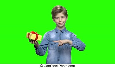 Boy in denim jacket holding yellow gift box and pointing...