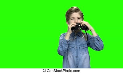 Boy in denim jacket looking through binoculars. Green...