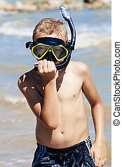 Boy in diving mask on the beach