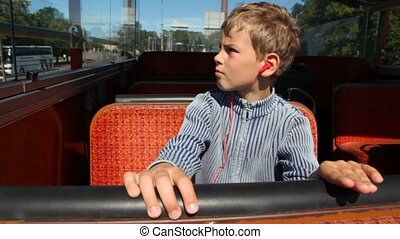 boy in earphones goes in empty bus around city close up
