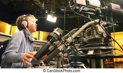 boy in earphones operating stationary camera in TV studio -...
