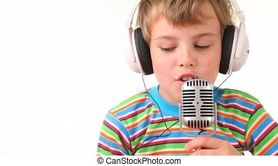 boy in earphones talking through microphone - happy boy in...