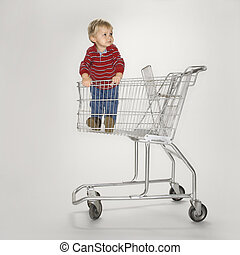 Boy in empty cart. - Studio portrait of Caucasian boy ...