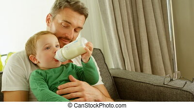 Boy in fathers lap drinking milk on sofa 4k - Boy in fathers...
